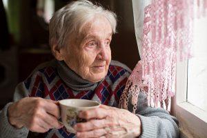 Elderly woman drinking tea sitting near the window.